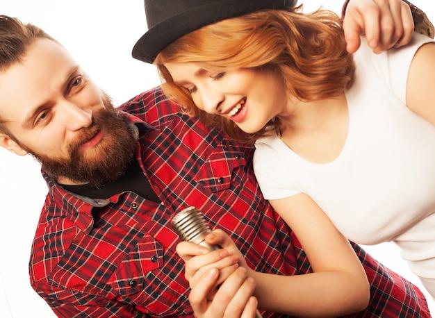 노래방 - 마이크가 있는 사랑스러운 커플. 젊고 아름다움. 힙 스터 스타일. 흰색 배경 위에.
