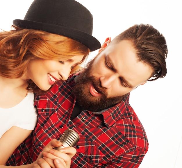 노래방 - 마이크가 있는 사랑스러운 커플. 젊고 아름다움. 힙스터 스타일. 흰색 배경 위에.