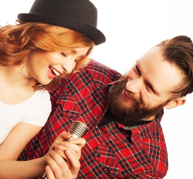 カラオケ-マイク付きの素敵なカップル。若くて美しさ。流行に敏感なスタイル。白い背景の上。