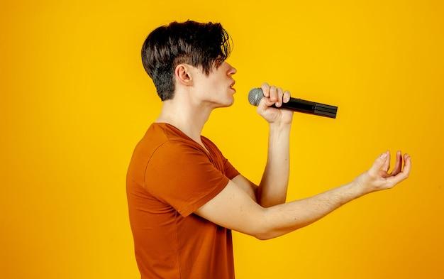 Караоке человек поет песню в микрофон, на желтом фоне. забавный человек держит микрофон в руке у певца караоке, поющего песню! пивец на желтом фоне