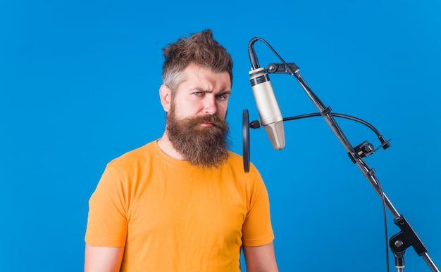 Караоке. человек поет с микрофоном. студия звукозаписи. бородатый мужчина поет в микрофон. микрофон. поет песню. пение в студии.