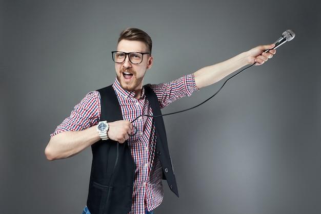 가라오케 남자는 마이크에 노래를 부르고 회색 배경에 수염을 기른 가수. 노래방 가수에서 손에 마이크를 들고 안경을 쓴 재미있는 남자가 노래를 부른다
