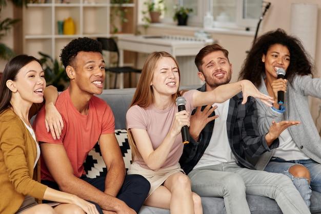 自宅でカラオケをしている陽気な若い多文化の友達のカラオケタイムグループと一緒に歌う