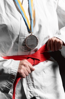 Atleta di karate con cintura rossa e primo piano della medaglia