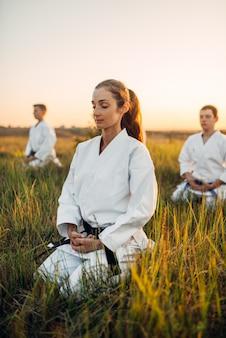 Karate class in white kimono meditates on training in summer field.