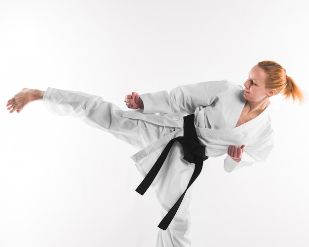 Karate fighter kicking on plain background