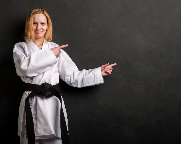 Karate fighter pointing at copy space