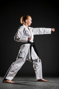 Karate girl practicing side view