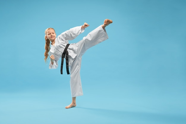 Karate girl in white kimono practicing martial arts.