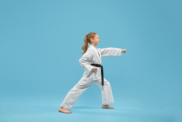 Karate girl with black belt practicing martial arts.