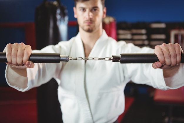 Karate player practicing with nunchaku