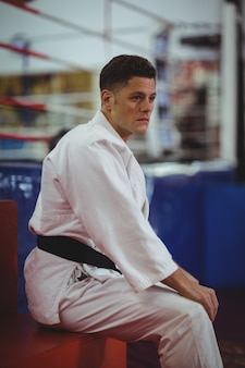 Karate player sitting in fitness club