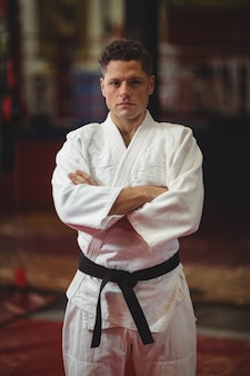 Karate player standing with arms crossed