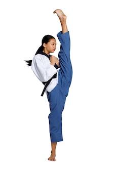 Каратэ тхэквондо девушка-подросток тренируется. боевой удар и высокая нога на уровне черного пояса. азиатская молодежная спортсменка женщина носит спортивную традиционную форму на белом фоне во всю длину изолированы