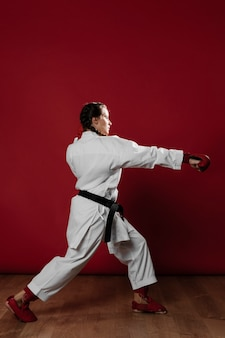 Karate woman in action isolated in red background