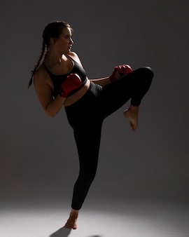 Karate woman giving a kick and dark background