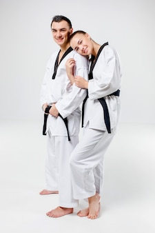 The karate woman and man with black belts