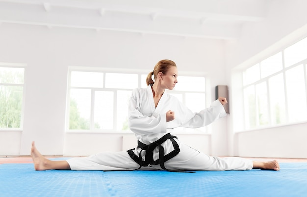 Karate woman, wearing in kimono stretching leg before hard workout.
