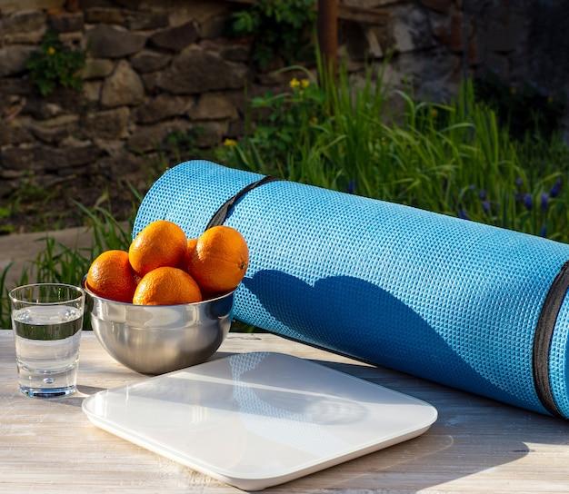 Каремат, мандарины, чешуя и стакан воды на деревянном столе на открытом воздухе