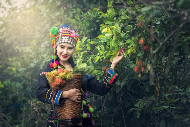 Karens girl with traditional clothes in rambutan plantation