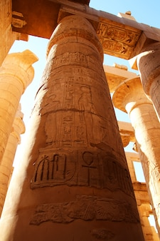Karnak temple complex in luxor. polychromed columns with carvings of the pharaoh and his wife