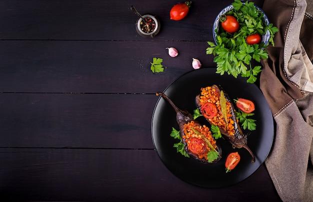 Karniyarik-トルコの伝統的な子egg子の食事。ナスとトマトソースで焼いた野菜を詰めたナス。トルコ料理。上面図。コピースペース