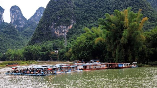 Карстовые вершины в городе синпин и прогулочные катера на реке ли, известной как река лицзян.