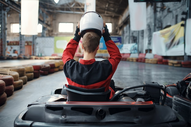 Kart racer puts on helmet, back view, karting indoor.