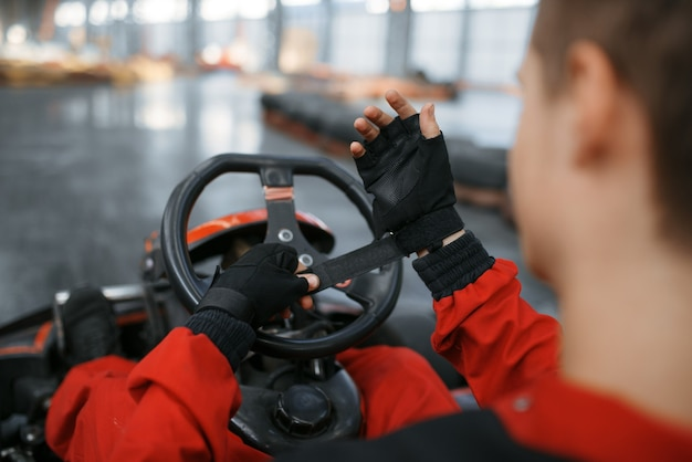Kart racer in red uniform puts on gloves, karting auto sport indoor.