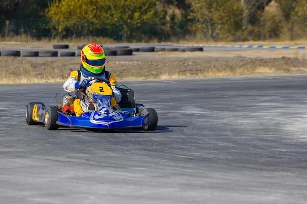 Karting driver in helmet on kart circuit