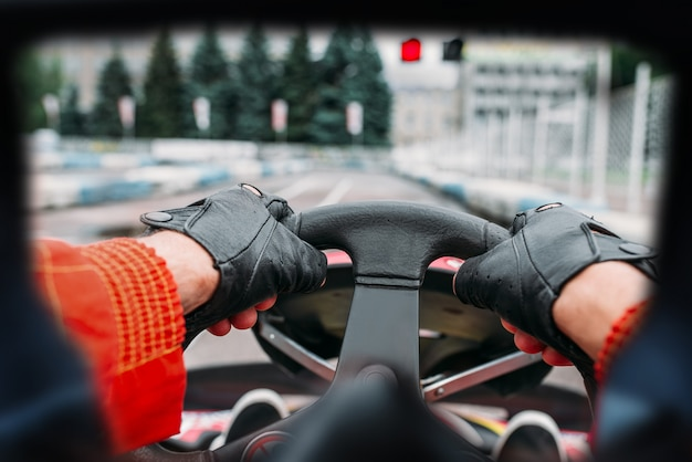 Karting driver on start line, view through the eyes of the racer. go-kart speed track