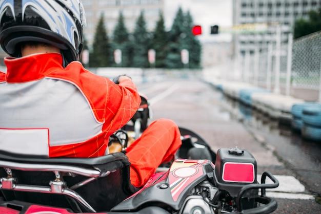 Karting racer, go kart driver in helmet, back view. carting speed track