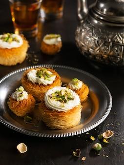 Kataifi、kadayif、kunafa、バクラヴァペストリーは紅茶とピスタチオクッキーを入れ子にします。