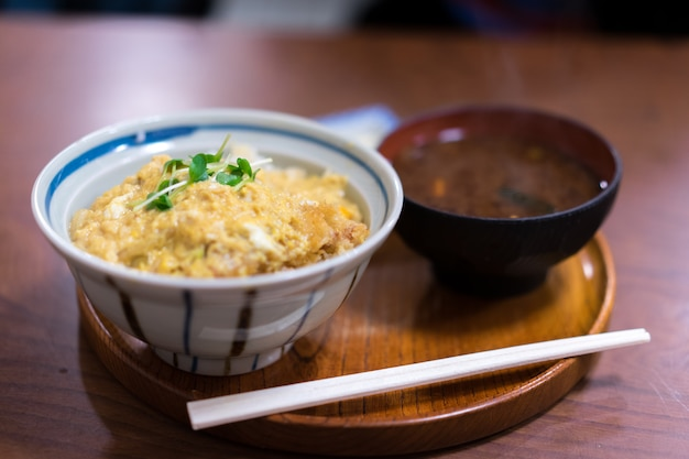 Katsudon served in a large japanese rice bowl with a pair of chopsticks.
