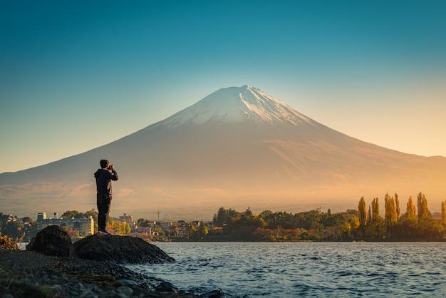 Вид сзади человека путешественника принимает фото гора фудзи и озеро kawaguchiko на заходе солнца в kawaguchiko, японии.