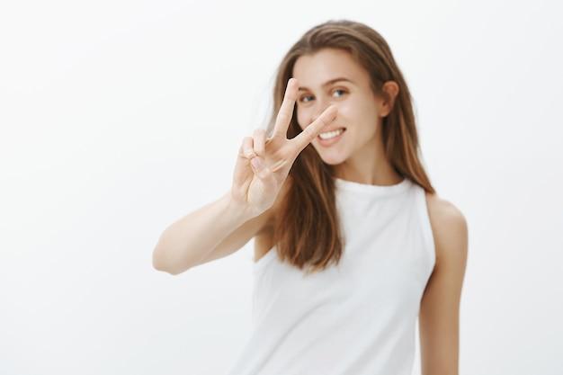 Kawaii giovane donna caucasica che mostra gesto di pace e sorridente con denti bianchi