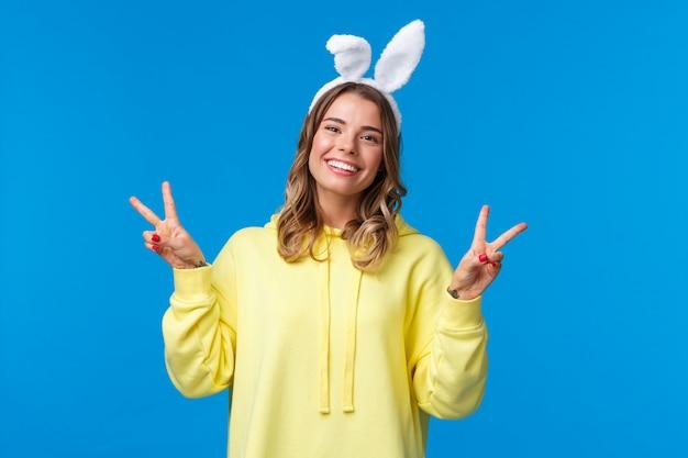Праздники, традиции и концепция праздника. молодая блондинка kawaii в ушах кролика показывает мирный жест и улыбается, веселиться, наслаждаться вечеринкой, стоя синей стеной