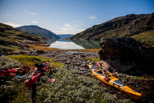 Kayak expedition between icebergs in narsaq fiords, south west greenland, denmark