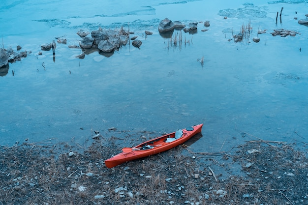 Kayak lies on a wild beach of a wild lake