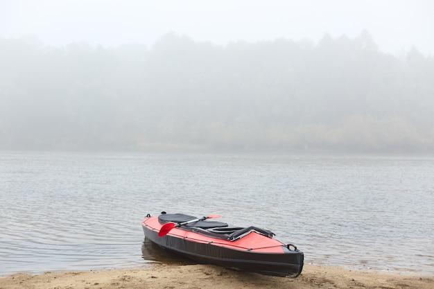 Каяк на берегу реки в туманное раннее утро