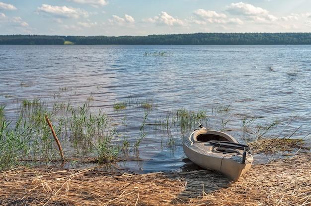 Каяк на песчаном берегу озера в яркий солнечный день естественный свет