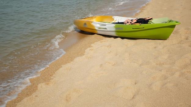 바다 파도에 의해 모래에 패들과 카약. 물, 열대 해변, 여름 휴가로 다채로운 카누.
