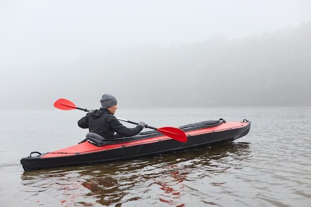 Каякер, гребля в воде, держа в руках весло