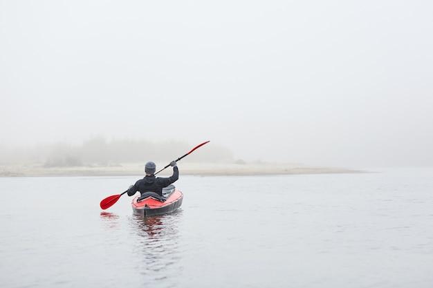 Каякер гребная лодка к берегу реки, держа в руках весло. в теплой одежде