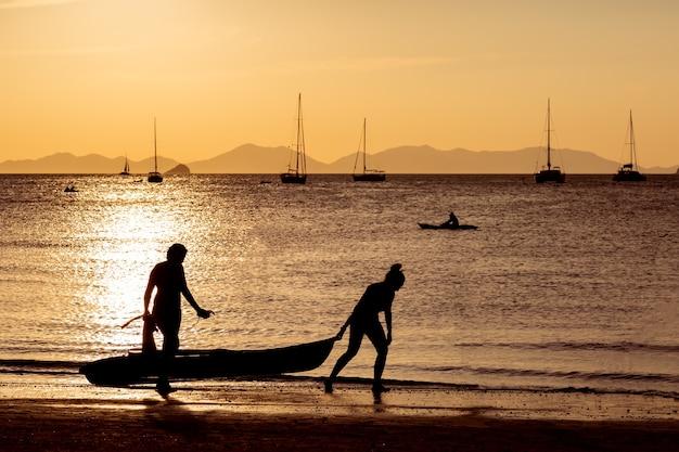 Каякеры плывут по воде, две девушки выносят на берег лодки яхту и горы