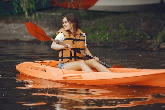 カヤック。カヤックの女性。水を漕ぐ少女。
