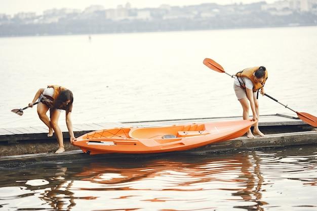 카약. 카약을 탄 여성. 소녀들은 호수에서 패딩을 준비합니다.
