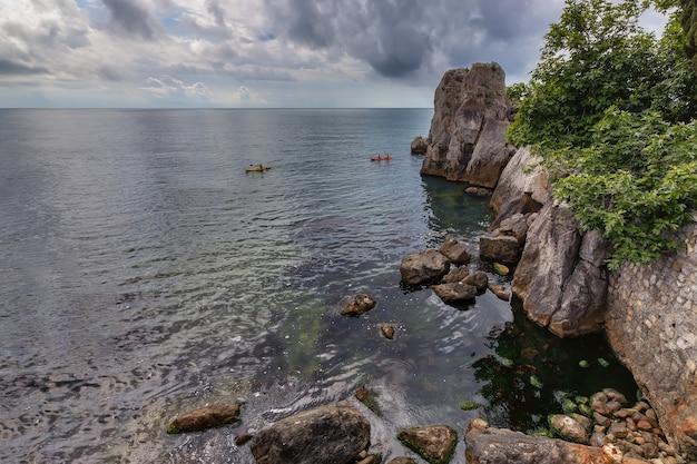 カヤックカヤック休暇の背景ベイビーチ美しい美しさ黒い海の崖の崖の端 Premium写真