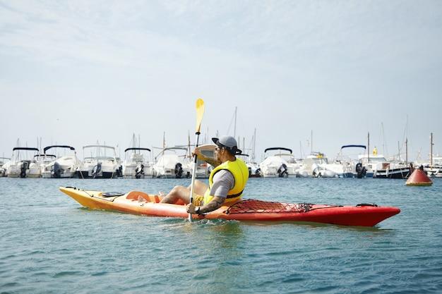 Kayaking man in cap and yellow safety jacket