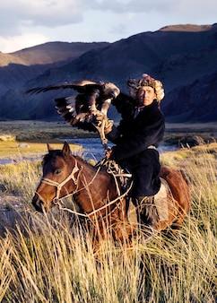 カザフスタンの男性は、伝統的に狐とオオカミを訓練されたゴールデンワシを使って狩る。西モンゴルのオルゲイ。